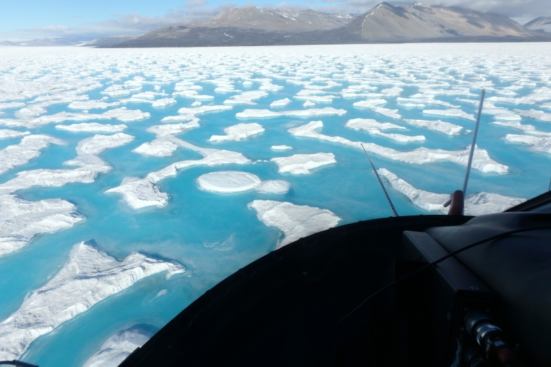 A view looking out the helicopter window at the frozen freshwater pools on top of the Ross Ice Shelf. Above the Ross Ice Shelf approaching Garwood Valley, Antarctica.