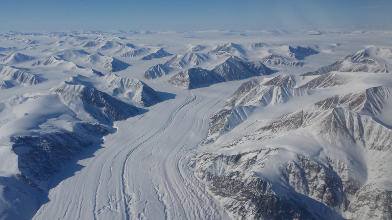 Glacial ice twists and turns through the rough terrain of Greenland, with tributary glaciers merging into larger trunk glaciers flowing slowly toward the coast. Aboard the WP-3D Orion over the Greenland Ice Sheet.