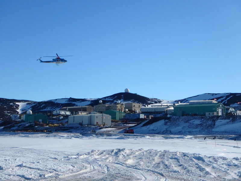 A helicopter descends towards the landing pad at McMurdo Station, Antarctica.